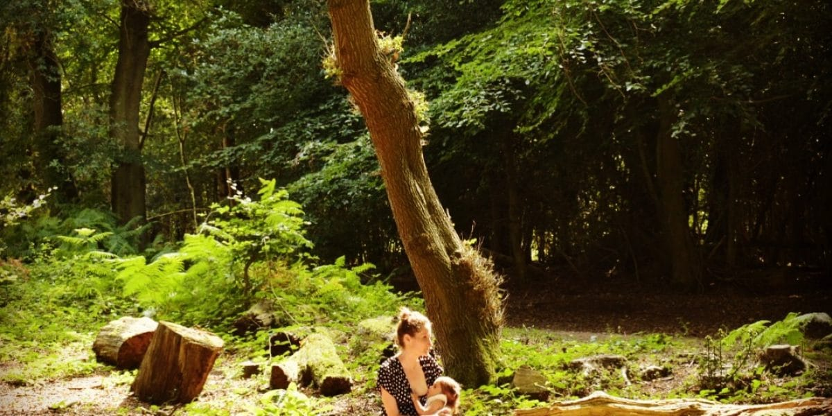 Photo of breastfeeding in a forest.